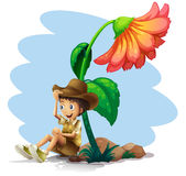 A boy wearing a hat sitting below the giant flower Stock Image
