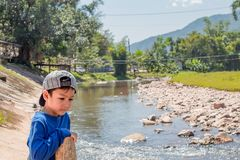 A boy wearing a hat standing water and rocks in a stream stock photos