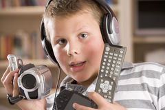 Boy wearing headphones holding electronics Royalty Free Stock Photography