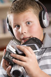 Boy wearing headphones holding many electronics Royalty Free Stock Images