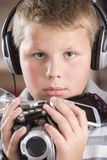 Boy wearing headphones holding many electronics Stock Photos