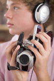 Boy wearing headphones holding many electronics Stock Images