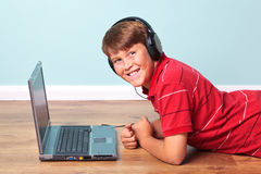 Boy wearing headphones with laptop royalty free stock photos