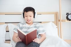 Boy wearing headset and reading book on bed Stock Photo