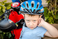 A boy wearing a helmet next to motorcycle Stock Photo