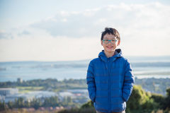 Boy wearing jacket and smiling outdoor. Young asian boy wearing blue jacket and smiling outdoor Stock Image