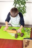 Boy wearing a kitchen apron rolling a brown dough with a wooden rolling pin on a silicone green pastry board. A child in the kitch. En. Little cook. The boy royalty free stock image