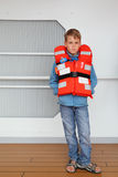 Boy wearing in life jacket stands at deck of ship. Serious boy wearing in orange life jacket stands at deck of ship royalty free stock image