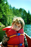 Boy wearing a lifejacket. Child in a canoe wearing a life jacket Stock Images