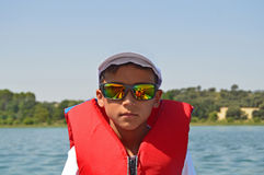 Boy Wearing A Lifejacket. A boy wearing a buoyancy aid with a reflection of the boat in his sunglasses Royalty Free Stock Images