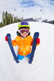 Boy wearing mask and helmet holds ski in winter Royalty Free Stock Photo