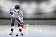 Free Boy Wearing Mask Practicing Hockey Skills At Empty Ice Rink During COVID-19 Pandemic Royalty Free Stock Photography - 194695447