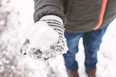 A boy wearing mittens, wool gloves holding a snowball in his hand, outdoor winter activities concept stock image