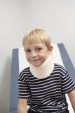 Boy Wearing Neck Brace. Portrait of a cute boy wearing neck brace in the clinic royalty free stock photos
