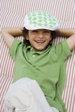 Boy Wearing Newsboy Cap. Portrait of a young boy wearing newsboy cap while relaxing on mattress Royalty Free Stock Photos