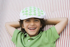 Boy Wearing Newsboy Cap. Portrait of a young boy wearing newsboy cap while lying on mattress Royalty Free Stock Photo
