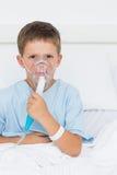 Boy wearing oxygen mask in hospital ward. Portrait of little boy wearing oxygen mask in hospital ward Stock Image