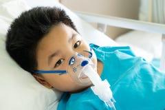Boy wearing oxygen mask. Boy wearing oxygen mask in hospital ward. Selective focus stock photos