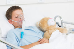 Boy Wearing Oxygen Mask Sleeping Beside Teddy Bear Royalty Free Stock Photography