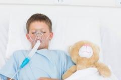 Boy wearing oxygen mask sleeping beside stuffed toy Stock Photos