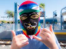 Boy Wearing Peru Waq'ollo Wool Knit Mask At Train Station In Santa Monica. Boy wearing a Peruvian Waq'ollo knit wool face mask. Rainbow striped knitted mask with Stock Photos