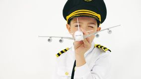 Boy wearing pilot`s uniform plays with toy airliner. Boy wearing pilot`s uniform plays with toy plane stock footage