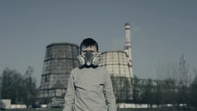 Boy wearing a respirator against factory chimneys. Air pollution concept.