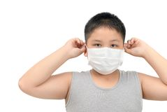 Boy wearing protective mask to protect pollution and flu. Obese fat boy wearing protective mask to protect pollution and the flu isolated on white background stock photo