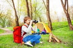 Boy wearing red backpack watches through binocular Royalty Free Stock Photos