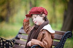 Boy Wearing Red Beret Cap While Sitting on Bench royalty free stock photography