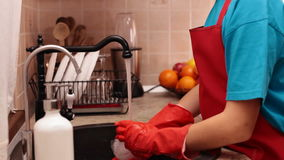 Boy wearing rubber gloves washing a glass stock footage
