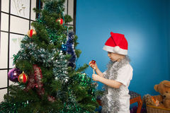 Boy wearing santa claus clothes with a gift Royalty Free Stock Image