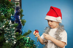 Boy wearing santa claus clothes with a gift Royalty Free Stock Images