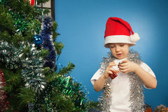 Boy wearing santa claus clothes with a gift Royalty Free Stock Photos