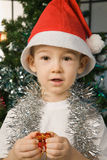 Boy wearing santa claus clothes with a gift Stock Image