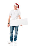 Boy wearing Santa Claus hat. Caucasian man wearing christmas hat for santa. Teenager in white t-shirt with blank sign isolated on white background. Successful Royalty Free Stock Photo