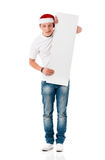Boy wearing Santa Claus hat. Caucasian man wearing christmas hat for santa. Teenager in white t-shirt with blank sign  on white background. Funny boy wearing Royalty Free Stock Photography
