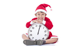 Boy wearing Santa Claus uniform and holding clock Royalty Free Stock Photos
