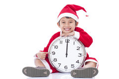 Boy wearing Santa Claus uniform and holding clock Stock Photography