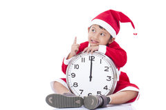 Boy wearing Santa Claus uniform and holding clock Royalty Free Stock Photo