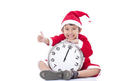 Boy wearing Santa Claus uniform and holding clock Stock Photos