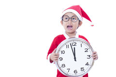 Boy wearing Santa Claus uniform and holding clock Royalty Free Stock Image
