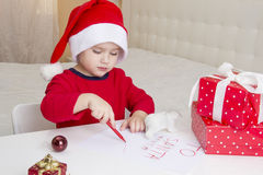 Boy wearing Santa hat, writing a letter to Santa Stock Images