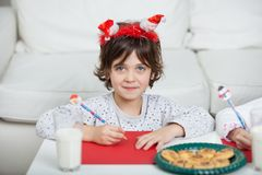 Boy Wearing Santa Headband Writing Letter At Home Stock Photography