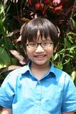 Boy wearing spectacle. Smiling boy in blue shirt wearing black-frame spectacle Stock Images