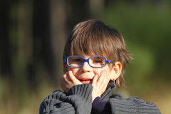 Boy wearing spectacles. Portrait of young boy wearing spectacles and holding face with surprised expression Royalty Free Stock Image