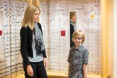 Boy Wearing Spectacles While Mother Looking At Him Royalty Free Stock Photos
