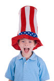 Boy wearing stars and stripes. Young boy wearing a stars and stripes patriotic top hat with a funny expression on his face Royalty Free Stock Photography