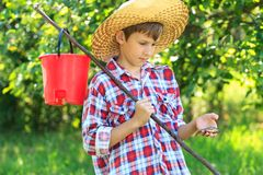 Boy wearing straw hat looking at caught fish Stock Images
