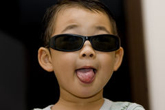 Boy wearing sun-glasses. Picture of a little chinese boy wearing sun-glasses and making faces Royalty Free Stock Images